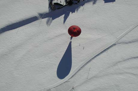 The balloons envelope casting a shadow on to the ground in the snow.