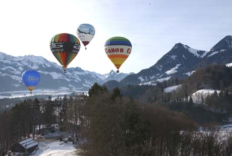 A selection of different company balloons (Canon etc) flying over the Swiss Alps.