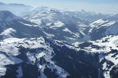 Serene, quiet beauty as a hot air balloon flies over the Alps of Switzerland.