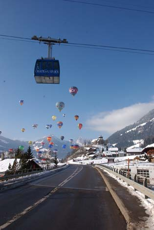 The hot air balloons taking off over a cable car.