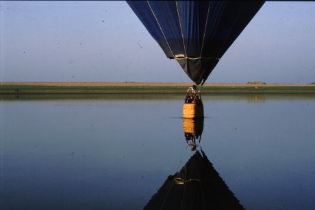 A hot air balloon flight ends with a landing on a lake.
