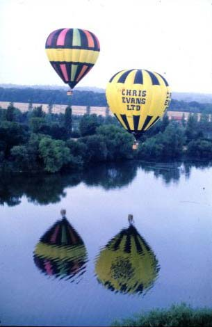 Two hot air balloons flying together over a river.