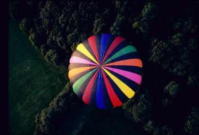 Birds eye view of a colourful hot air balloon envelope as seen from another hot air balloon.