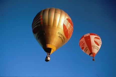 In the foreground is a standard hot air balloon and in the background you can see a one man balloon.