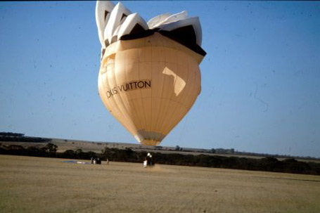 A hot air balloon shaped as the Sydney Opera House comes in to land.