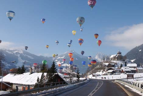 The hot air balloons flying over the road in the ski resort.