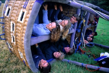 Passengers laying on their sides as the hot air balloon basket makes a landing.
