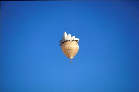 A hot air balloon shaped as the Sydney Opera House as seen from far away.