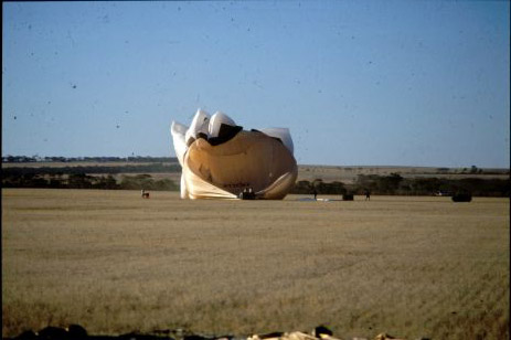 A hot air balloon shaped as the Sydney Opera House has landed and the envelope has completely collapsed.